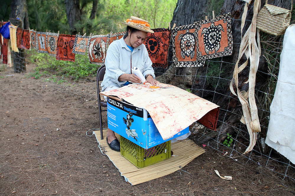 A local woman finishes a print on hand made paper at a roadside stand on the North Shore of Oahu, Hawaii. Photo by Matt May