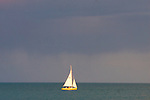 A single small sailboat is adrift on the open water of Lake Michigan as storms approach.