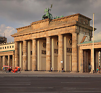 The Brandenburg Gate or Brandenburger Tor, 18th century, a neoclassical triumphal arch marking one of the old city gates of Berlin, at the end of Unter den Linden, Berlin, Germany. The gate was commissioned by King Frederick William II of Prussia as a sign of peace and built by Carl Gotthard Langhans 1788-91. It stood inaccessible next to the Berlin Wall during Germany's Partition and was restored 2000-02 by the Stiftung Denkmalschutz Berlin. It consists of 12 Doric columns and is topped by a statue of a quadriga, a chariot pulled by 4 horses. Picture by Manuel Cohen