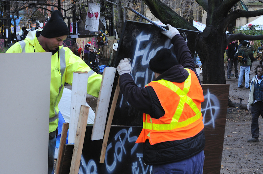 November 23, 2011, Toronto Police arrived in significant numbers early this morning, beginning the process of evicting the Occupy Toronto tent camp from St. James Park.  Here city workers are seen dismantling a profane sign near the band shell.
