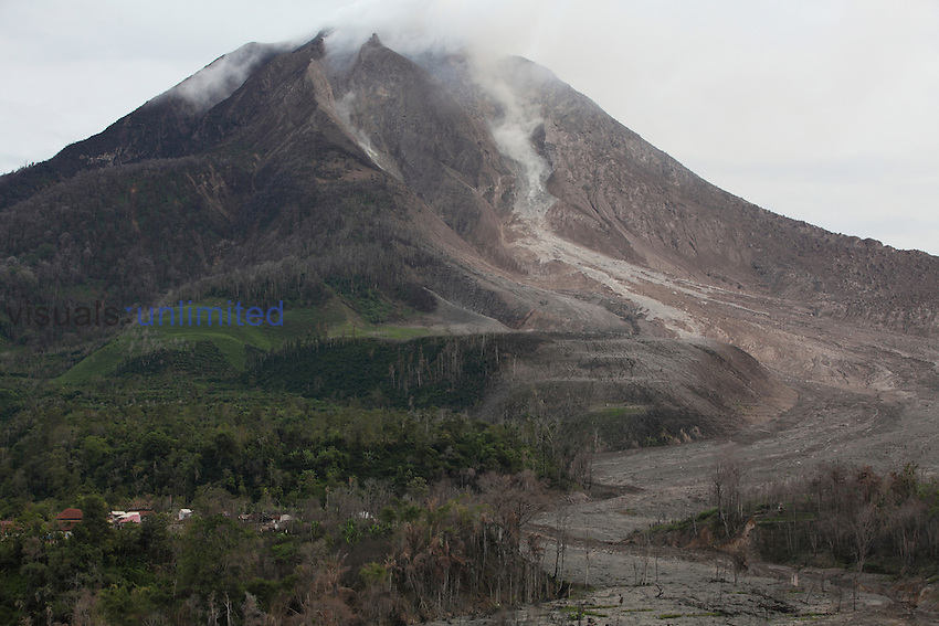 Sinabung Volcano with andesite lava dome at summit and lava flow deposits above evacuated village, Sumatra, Indonesia