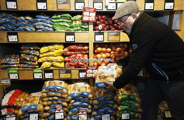 Foto: VidiPhoto<br /> <br /> ZETTEN – Wim Janssen uit Zetten in de Betuwe, pakt een zak aardappelen in kleinverpakking uit het schap van supermarkt Jumbo.