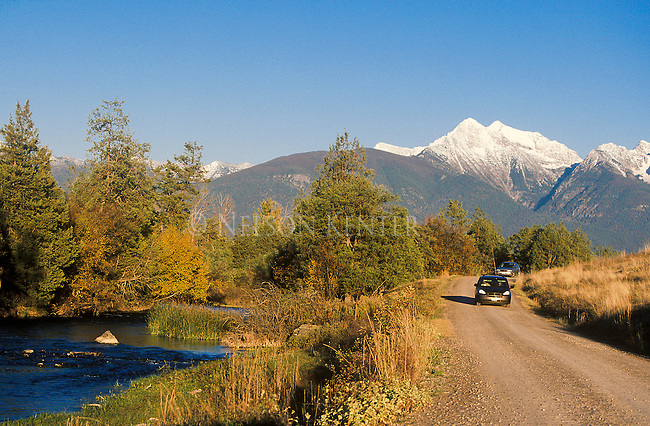A vehicle driving through the National Bison Range in Montana with the snow capped Mission Mountain Peaks across the valley