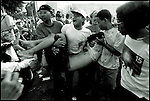 Summer '99-- Jakarta, Indonesia -- Men carry a guy who fell over 70 feet into the peoples pond while trying to put up a party flag to show supporters their fervor for their parties candidate.