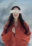 Artistic portrait of a beautiful asian woman with red sensual lips wearing a red undone kimono standing in the snow with a long black hair and a blindfold over her eyes