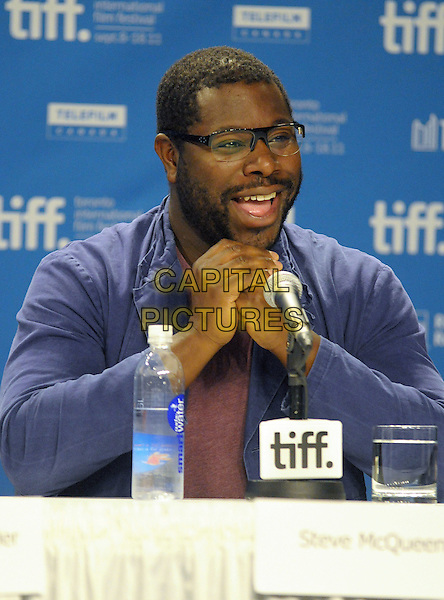 "Steve McQueen.""Shame"" Press Conference - 2011 Toronto International Film Festival held at TIFF Bell Lightbox, Toronto, Ontario, Canada..September 12th, 2011.half length smiling microphone speech hands mouth open blue shirt pink beard facial hair glasses.CAP/ADM/BPC.©Brent Perniac/AdMedia/Capital Pictures."