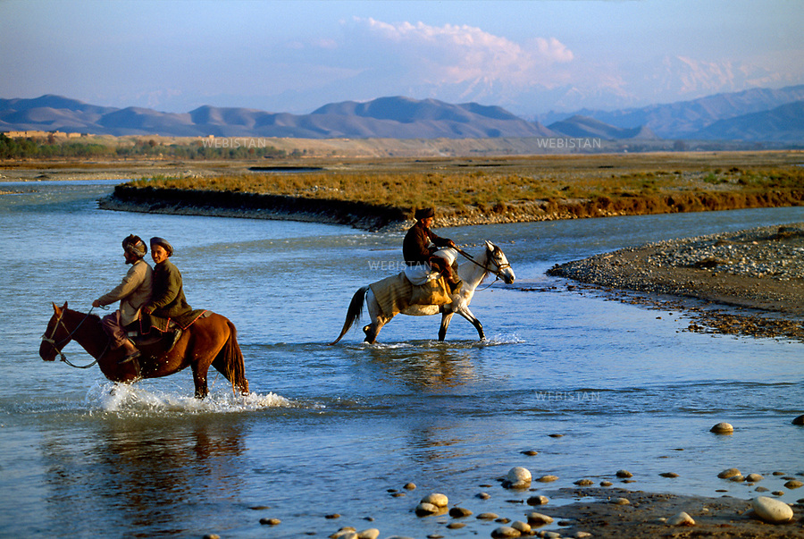 Afghanistan. Takhar Province. 2000. Horsemen cross the Kokcha River near the border with Tajikistan in the background. <br /> <br /> Afghanistan. Province du Takhar. 2000. Des cavaliers traversent la rivi&egrave;re Kokcha pr&egrave;s de la fronti&egrave;re avec le Tadjikistan en arri&egrave;re-plan.