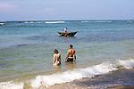 Tourists bathing in sea man fishing using traditional outrigger canoes, Mirissa, Sri Lanka, Asia