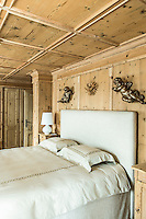 A pair of cherubs hang on the wood panelled walls above the bed in the chalets master bedroom