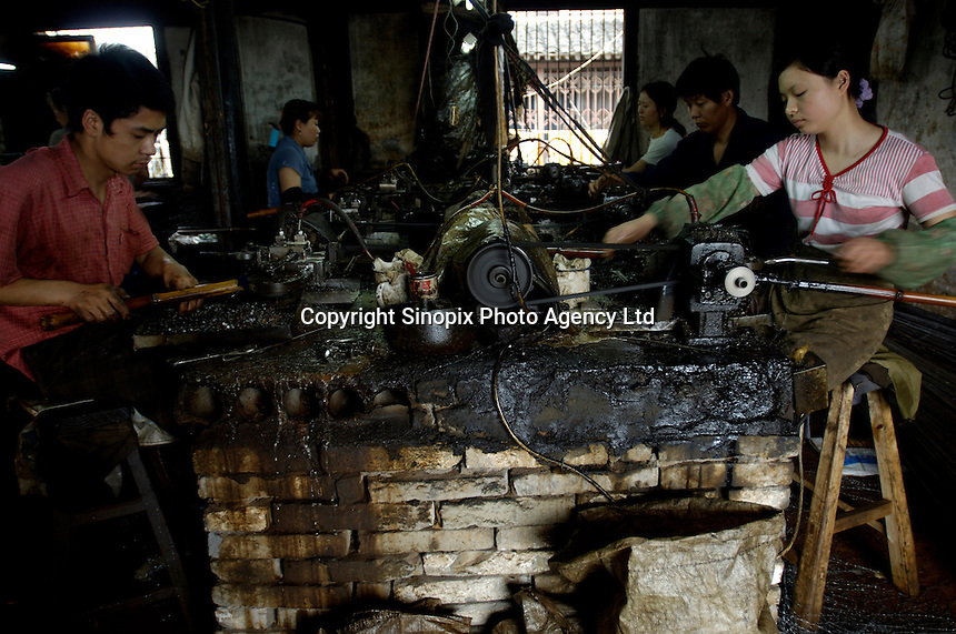 Chinese workers, mostly from western China,  produce metal components for export in a poor-conditioned private metal-work factory in coastal Ningbo, Zhejiang province, China..