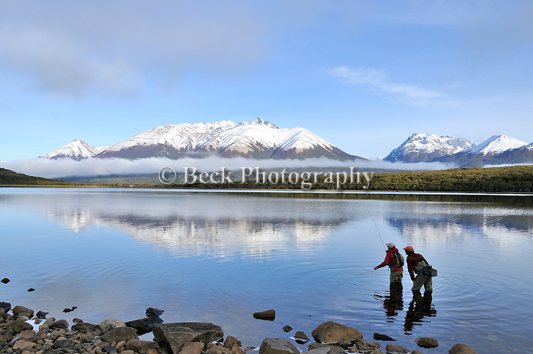 You can see the reflection of the snow capped mountains mirrored in the lake at Tres Valles, Patagonia, Argentina as the anglers fish.