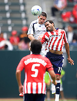 ChivasUSA forward Maykel Galindo (11) and NE Revolution defender Jay Heaps (6) battle in the air for a ball as Chivas midfielder Paulo Nagamura (5) defends during the first half of a MLS game. The New England Revolution defeated the Chivas USA 2-1 at Home Depot Center Stadium, in Carson, Calif., on Sunday, May 11, 2008.