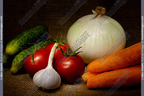 Light-painted colorful vegetable country-style still life with tomatoes, onion, cucumbers, carrots and garlic on sacking fabric background