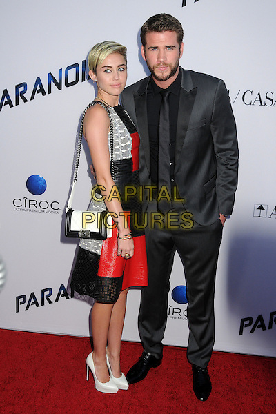 Miley Cyrus, Liam Hemsworth<br /> &quot;Paranoia&quot; Los Angeles Premiere held at the Directors Guild of America, West Hollywood, California, USA, 8th August 2013.<br /> full length red black leather dress sleeveless perforated silver bag white shoes couple fiance fiancee engaged grey gray suit black shirt tie arm around grey gray snakeskin <br /> CAP/ADM/BP<br /> &copy;Byron Purvis/AdMedia/Capital Pictures