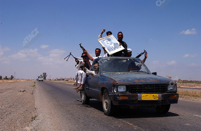 Men celebrating the birthday of Saddam Hussein drove down the road south of Tikrit to Baghdad firing bullets into the sky as small groups of loyalists of the former Iraqi president went onto the streets in the area around his hometown to mark the day. April 28, 2003