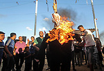 Palestinian protesters burn a doll wearing a mask depicting US President Donald Trump's face during clashes with Israeli troops in tents protest where Palestinians demand the right to return to their homeland at the Israel-Gaza border, in east of Gaza city on September 7, 2018. Photo by Dawoud Abo Alkas