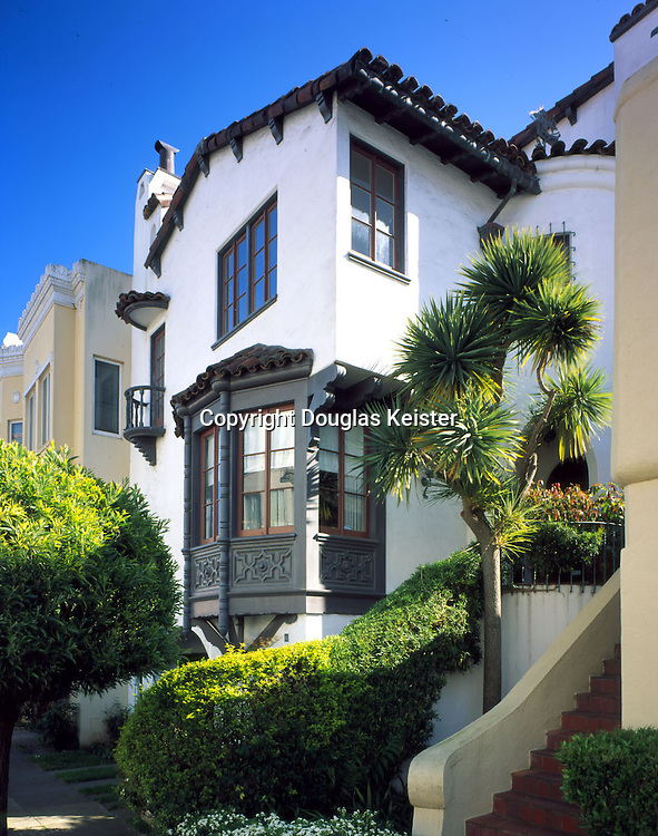 The Marina District is also the setting for this elegant and unusual Spanish Revival home dating from the late Twenties.  Its focal point is a spectacularly crafted asymmetrical bay window of almost Elizabethan complexity, with turned wooden mullions and ornamental spandrel panels carved in low relief, all of which are supported on a radiating set of scrolled wooden brackets.  At background is a tiny mirador carried on wooden corbels, its half-round spindled railing reflected by the tile-capped hood above.  Also of note are the array of blunt wooden brackets under the bargeboard and the overhanging fringe of barrel tile at the eave, both of which depart from the Spanish Revival's usual preference for a clean-cut roofline.