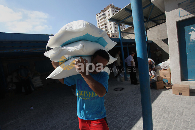 A Palestinian man carries bags of flour he received at a distribution centre of the United Nations Relief and Works Agency (UNRWA) in Gaza City on August 11, 2014. An Israeli delegation arrived in Cairo for indirect negotiations with Palestinians on a durable truce in Gaza, Egypt and Israeli officials said. Photo by Ashraf Amra
