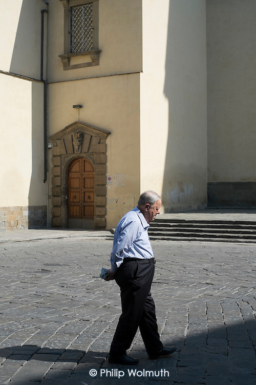 Elderly man with a newspaper walking in a cobbled square, Florence, Italy.