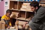 Preschool 3-4 year olds male teacher working with boy building with wooden blocks in block area horizontal