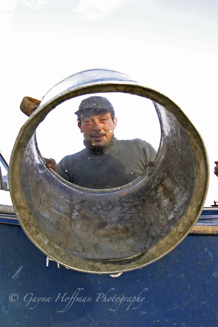 Sicilian fisherman looking through glass-bottomed barrel used for night fishing. Sicily, Italy