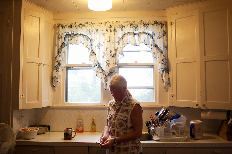 Wellsville, Kansas, May 28, 2011 - Fourth generation family farmer Robin Dunn makes a call after breakfast in the kitchen of her farm, Dunn's Landing. She bought her great grandparents homestead from her father in 1993, and today grows soybeans, corn, sorghum and hay, and maintains a small herd of Black Angus cattle and eight horses which she uses to for wagon and stage coach rides.  According to the most recent Department of Agriculture data, there are more than 306,000 farms run primarily by women in 2007, representing about 14 percent out of the 3.3 million American farms.  That's up from 237,819 or 11 percent in 2002, and a big increase from the 1980s when about five percent of U.S. farms were operated by women.Dunn has branched out from her farming business, using her century-old dairy barn to host 25 to 30 weddings and other events a year. She also attracts tourists for farm tours and carriage rides, and holds sessions with school children to teach them about faming.