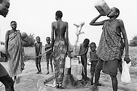Sudan. Southern part. Bahr El Ghazal. Panthou. Dinka tribe area. Water pump and well restoration by UNICEF and the Swiss Development Agency (SDA). Children fill a water tank while a woman drinks from a water container. © 1998 Didier Ruef
