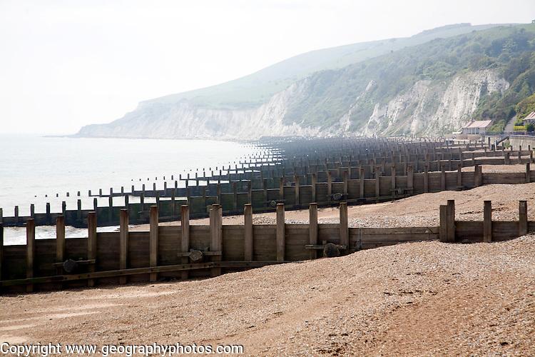 Wooden groynes on Eastbourne beach, looking west towards Beachy Head chalk cliffs, East Sussex, England