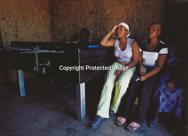 LSSHEBE30035.Life Style. Shebeen. Eastern Cape. Rural. People (women) sitting next to a soccer game machine, one of them in the middle has a stocking (pantihose) on her head having a beer and a cigarette. .©Per-Anders Pettersson / iAfrika Photos