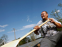 Gabriel Yanes paddles his boat through the Red Star District of Cape Girardeau, MO, on Thursday, April 28, 2011.