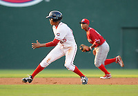 Outfielder Henry Ramos (25) of the Greenville Drive stops just past second base to avoid a pickoff in a game against the Lakewood BlueClaws on July 12, 2011, at Fluor Field at the West End in Greenville, South Carolina. (Tom Priddy/Four Seam Images)