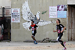 Participants run in the biblical West Bank town of Bethlehem during the 5th Palestine Marathon on March 31, 2017. Photo by Wisam Hashlamoun