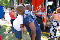 African American firefighter greets old friend at firefighting demonstration. Aquatennial Beach Bash Minneapolis Minnesota USA