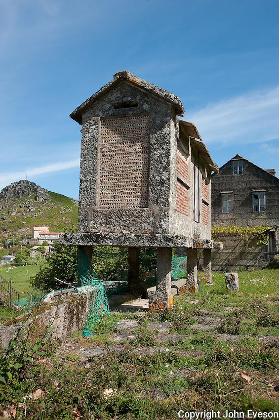"""Horreo. Typical stone built granary for storage and vermin protection, Chandebrito, Vigo, Galicia, Spain. They are raised off the ground by stone pillars known as """"pegollos"""", which can be made of either wood or stone. The sides are usually slatted for ventilation. They are found throughout north-east Spain , though particularly in Asturias and Galicia . They tend to be square in the former and rectangular in the latter.  These days very few are still used as granaries. Some are used to keep firewood or even the car dry, or as a shed to store bikes and general storage. Some lie abandoned. Some have been restored as folk monuments. They are often several or more in each village...Copyright..John Eveson,.Dinkling Green Farm,.Whitewell,.Clitheroe,.Lancashire..BB7 3BN.Tel. 01995 61280.Mobile 07973 482705.j.r.eveson@btinternet.com.www.johneveson.com"""
