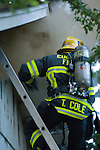 Emergency response: House fire: fire fighter with chain saw on ladder