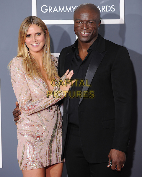 HEIDI KLUM & SEAL.Arrivals at the 52nd Annual GRAMMY Awards held at The Staples Center in Los Angeles, California, USA..January 31st, 2010.grammys half length pink white sequins sequined dress plunging low cut neckline cleavage long sleeves black suit married husband wife hand on chest butterfly ring .CAP/RKE/DVS.©DVS/RockinExposures/Capital Pictures