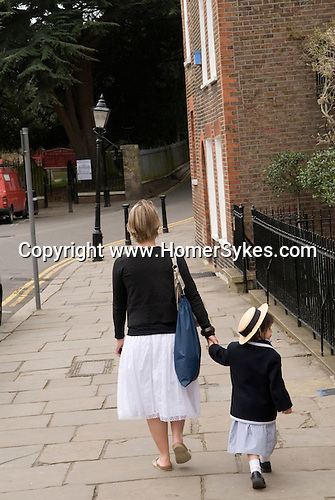 Mother and daughter holding hands walking home. Church Row, Hampstead, London NW3. England. 2006