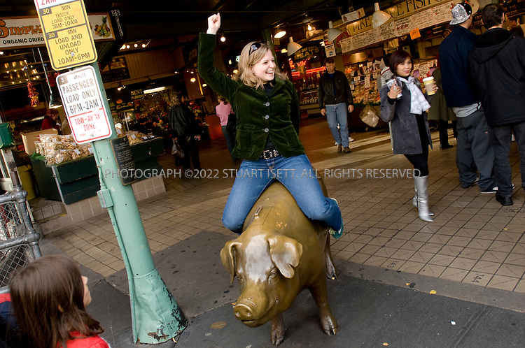 10/17/2007--Seattle, WA, USA..A ride on 'Rachel the Pig' at Pike Place Market is free. The market is a public market overlooking the Elliott Bay waterfront in Seattle, Washington, United States. The Market, which opened August 17, 1907, is one of the oldest continually-operated public farmer's markets in the country. It is a place of business for many small farmers, craftspeople and merchants...©2007 Stuart Isett. All rights reserved