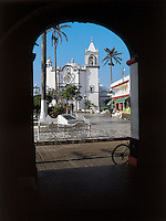 View of the main plaza of Tlacotalpan seen through the arches of the munincipal building, the floor of the plaza is made of marble.  The colonial port of Tlacotalpan is one of the best preserved small cities in mexico, it was declared a World Heritage town.  It is also the epicenter of the Cuban-Spanish influenced  Son Jarocho music.