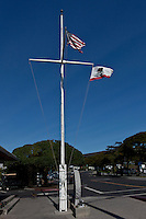 The United States flag and California State flag wave from a ship's mast styled flag pole at Pillar Point Marina south of San Francisco, California.