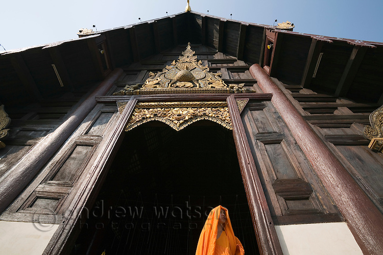 A monk stands in the entrance to Wat Phan Tao.  Chiang Mai, Chiang Mai province, THAILAND