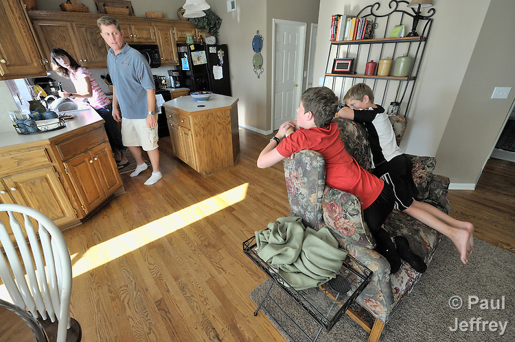 Brenda and Todd Mitton talk with their sons Grant, 13, and Blake, 10, in their Kearney, Missouri, home. Todd's work with the Missouri Air National Guard often requires him to be gone away from home for long periods of time.