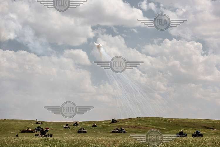 Smoke trails, from what a soldier claimed was a cluster bomb, hang in the air above military vehicles in a corn field, during a new offensive on ISIS positions in the northwestern part of Mosul.