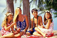 Mother with her part Hawaiian kids eating crack seed snacks at Kailua beach