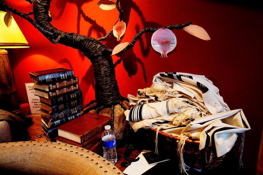 Los Angeles, California, March 20, 2011 - Torahs and Tallits (Jewish prayer shawls) on at table during a Purim carnival at Morry's Fireplace, a lounge owned by Aish LA where young Jews can socialize and network with one another. ..Purim is a Jewish holiday that commemorates the deliverance of the Jewish people living in the Persian Empire from genocide at the hands of the political advisor, Haman, to the Persian King Ahasuerus, as documented in the Talmud's Book of Esther. It is celebrated by the reading of the Scroll of Esther or the Megillah, sending food gifts to friends, giving charity to the poor and celebrating with a festive meal. During the reading of the Megillah, when Haman's name is mentioned (which happens 54 times) the congregation engages in loud roars and the use of rattles in an effort to blot out his name. Today children and some adults dress in costume and masquerade to celebrate Purim. The custom is believed to have originated during the 15th century by Italian Jews influenced by the Roman carnival. One idea for the costumes is that God disguised his presence behind many of the natural events that happened during Purim. .