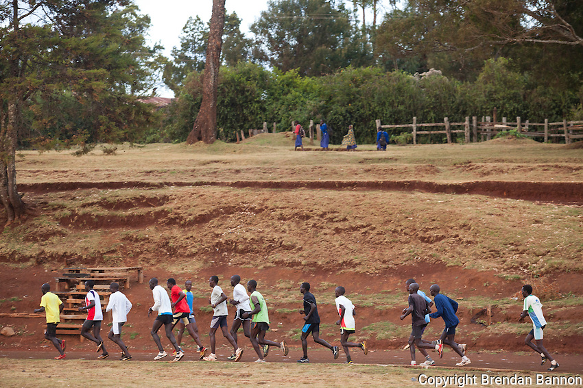 School children walk past as athletes train on a dirt track  in Iten, Kenya. The track is far from the standards of high tech training grounds and all-weather tracks of Europe and America. Increasingly speed-work is part of  the training for long distance races that has seen a revolution in marathon times since 2009. Young Kenyan runners  shifting from track to distance running are leading the revolution.