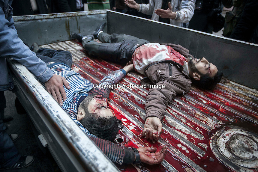 In this Monday, Dec. 03, 2012 photo, lifeless bodies of Syrian residents are taken to one hospital after they were killed during heavy shelling in Bustan Al-Pasha in Aleppo, the Syrian's largest city. (AP Photo/Narciso Contreras)