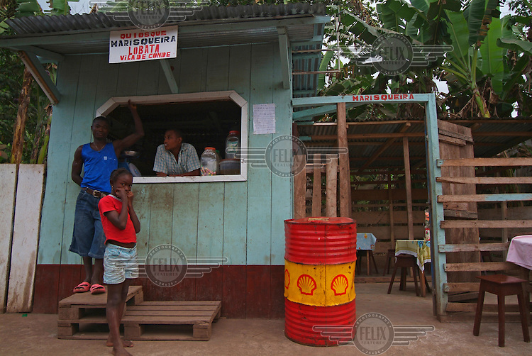 Small cafe with Shell oil drum outside.