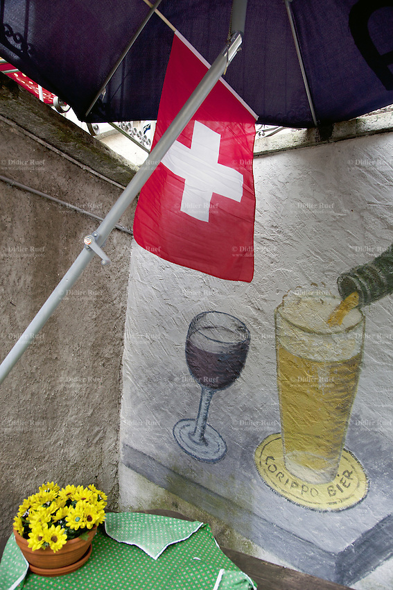 Switzerland. Canton Ticino. Corippo. Corippo lies in the Verzasca valley. Entrance of the unique restaurant in the village. A swiss flag, a table with a green plastic tablecloth, a flowerpot and on the wall sketches of two glases, one with red wine and the other with beer. With a population of just 16, Corippo is the smallest municipality in Switzerland. Despite this, it possesses the trappings of communities many times its size, such as its own coat of arms, a town council consisting of three local citizens and a restaurant. The village has maintained its status as an independent entity since its incorporation in 1822. The flag of Switzerland consists of a red flag with a white cross (a bold, equilateral cross) in the centre. 8.05.13 © 2013 Didier Ruef