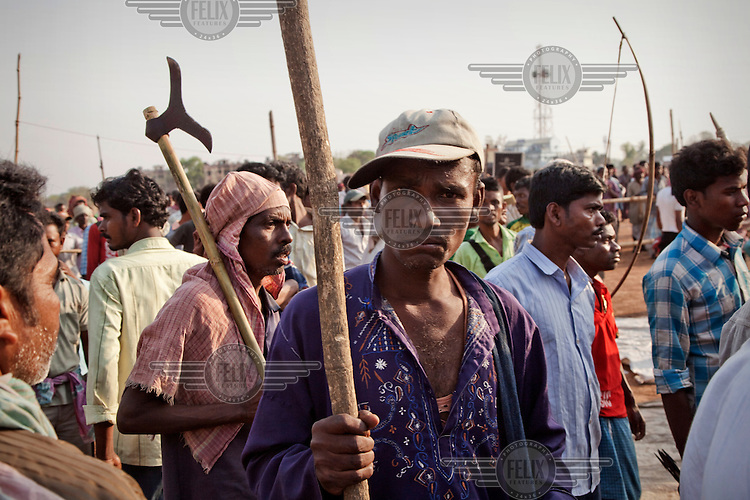 Men march holding bows and axes at a protest rally by Santal Adavesi tribespeople, on the West Bengal / Jharkhand border. They are demonstrating against the destruction of their land as a consequence of the excavation of a stone quarry.